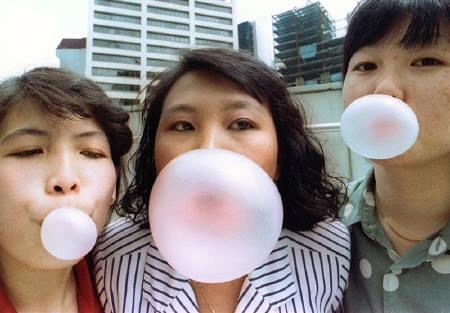 Singaporeans pose while blowing bubbles in this early January 1992photograph taken a few days before the city state banned gum. REUTERS/Jonathan Drake/Files