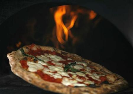 A pizza is removed from a wood-burning oven in this August 27, 2008 file image. REUTERS/Ciro De Luca/Agnfoto