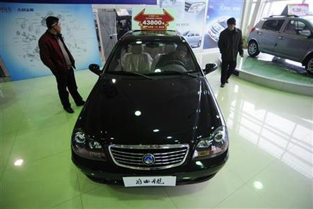 Visitors look at a car at a Geely flagship store in Hefei, Anhui province February 5, 2010. REUTERS/Stringer