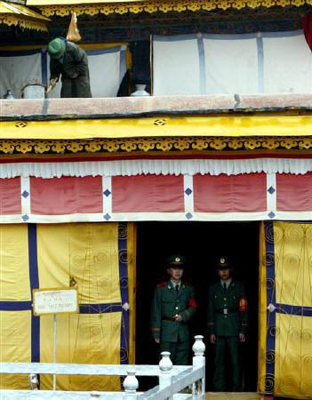 A Tibetan woman works on the roof as Chinese policemen guard anentrance inside Potala Place in Lhasa, Tibet, August 26, 2003. Tibetan high school students protested in the streets of at least two towns in western China this week to mark the anniversary of an uprising against Chinese rule.  REUTERS/Guang Niu/Files