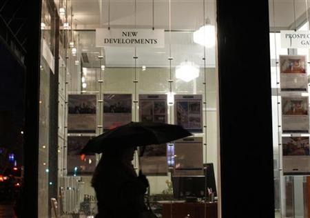 A commuter walks past a real estate office in Brooklyn, New York, February 23, 2010. REUTERS/Brendan McDermid