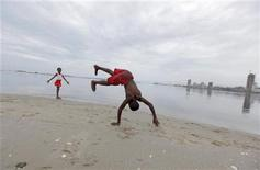 <p>Angolan youths play against the backdrop of the capital Luanda January 20, 2010. REUTERS/Mike Hutchings</p>