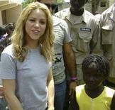 <p>Shakira ao lado de sobrevivente do terremoto em Porto Príncipe. A cantora colombiana teve um encontro no domingo com crianças que sobreviveram ao terremoto no Haiti, enquanto sua organização de caridade se prepara para construir uma escola no país caribenho devastado pela catástrofe. 11/04/2010 REUTERS/Noel Wilfrid</p>