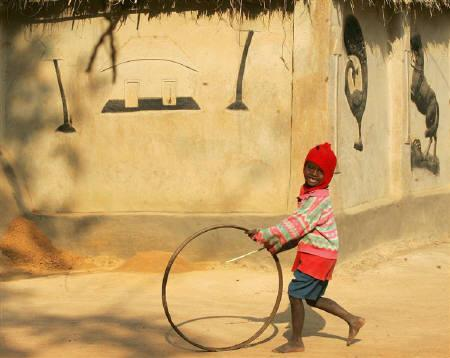 A tribal boy plays with an unused bicycle wheel in Santiniketan, about 165 km (103 miles) northwest of Kolkata in this December 11, 2005 file photo. REUTERS/Jayanta Shaw/Files