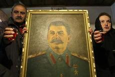 <p>People propose a toast, standing around a portrait of Soviet dictator Josef Stalin, in Stalin's hometown of Gori some 80 km (50 miles) west of Tbilisi March 5, 2010. REUTERS/David Mdzinarishvili</p>