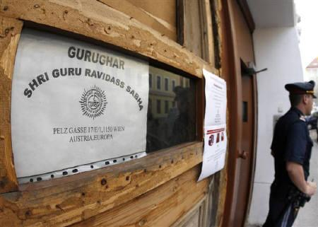 A police officer guards the entrance to the house where a Sikh temple is located in Vienna May 24, 2009. Austrian authorities have charged six men over the attack in which a visiting preacher died and which triggered deadly riots in India. REUTERS/Heinz-Peter Bader/Files