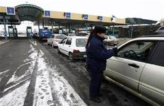 <p>A customs officer checks passports at the Horgos crossing at the Serbia-Hungary border, some 180km (111miles) north of Belgrade December 19, 2009. REUTERS/Djordje Kojadinovic</p>