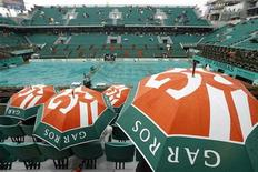 <p>Espectadores sentam com guarda-chuvas enquanto o jogo é interrompido no Aberto da França em Roland Garros, Paris. Com gotas de água ainda caindo nas áreas próximas, as coberturas foram retiradas das quadras e os jogos começaram nas principais quadras às 9h43 (horário de Brasília), quase cinco horas após o início previsto para a programação do dia. 27/05/2010 REUTERS/Regis Duvignau</p>