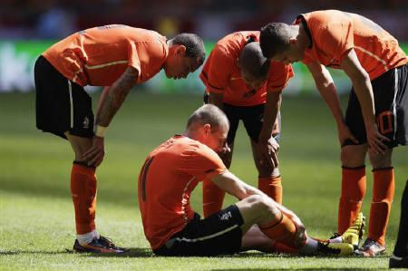 Arjen Robben of the Netherlands sits on the pitch surrounded by teammates Gregory van der Wiel (L), Nigel de Jong (C), and Ibrahim Afellay after injuring himself during their international friendly soccer matchagainst Hungary in Amsterdam June 5, 2010. REUTERS/Michael Kooren
