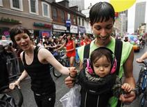<p>Lesbian couple and parents Julia Gonsalves and Andrea Bruner (L) hold their child Gracie Gonsalves-Bruner as they take part in an annual Gay Pride Parade in Toronto in this June 28, 2009 file photo. REUTERS/Mark Blinch</p>