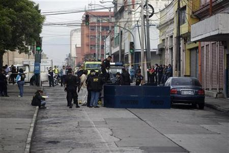 Police work at the crime scene where they found one of four severed heads left around Guatemala City June 10, 2010. According to the police, notes found with the heads point to prison gangs. REUTERS/Daniel LeClair