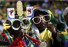 <p>Южноафриканские фанаты дудят в вувузелы на матче чемпионата мира по футболу между командами Мексики и ЮАР 11 июня 2010 год. Звук рожков вувузел, который не стихает в эти дни в ЮАР, где проходит чемпионат мира по футболу, стал самым популярным рингтоном для iPhone. REUTERS/Kai Pfaffenbach</p>