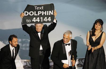 Director Louie Psihoyos (2nd R) accepts an award as cast member Richard O'Barry holds up a sign after ''The Cove'' won best documentary feature at the 82nd Academy Awards in Hollywood in this March 7, 2010 file photo. The film which deals with dolphin hunting, will be made available to Japanese viewers online. REUTERS/Gary Hershorn