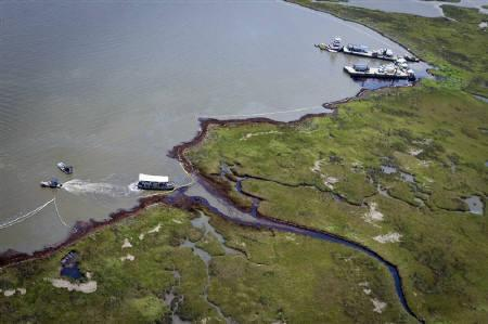 Work crews use booms and vacuums to clean marshland impacted by oil from the Deepwater Horizon Spill near Bay Jimmy, in the Barataria Bay of Louisiana June 17, 2010. REUTERS/Lee Celano