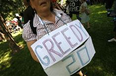 <p>A protestor carries a sign during a demonstration in Allan Gardens Park in downtown Toronto, Canada June 25, 2010 ahead of the G20 summit in Toronto. REUTERS/Mike Segar</p>