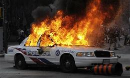 <p>A police car set on fire by anarchist demonstrators burns in the midst of protests on the streets of Toronto during the G20 summit June 26, 2010. REUTERS/Saul Porto</p>