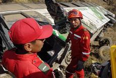 <p>Спасатели стоят рядом с обломками автобуса, перевернувшегося в 400 километрах к юго-востоку от города Ла-Пас, Боливия, 23 августа 2007 года. Как минимум 26 человек погибли и десятки получили ранения в результате крушения автобуса на горной дороге в Боливии в воскресенье, сообщила государственная радиостанция ABI. REUTERS/Danilo Balderrama</p>