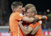 <p>Wesley Sneijder (dir) comemora com colegas de equipe após marcar gol contra a Esolováquia em Durban. Arjen Robben e Sneijder levaram a Holanda às quartas de final da Copa do Mundo com uma vitória confortável de 2 x 1 sobre. 28/06/2010 REUTERS/Michael Kooren</p>