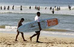 <p>A surfing instructor and his student head towards the Indian Ocean surf on Durban beach June 20, 2010. REUTERS/Paul Hanna</p>