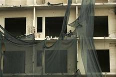 <p>A man sits on the balcony of a rundown building in Luanda January 27, 2010. REUTERS/Rafael Marchante</p>