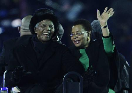 Former South African President Nelson Mandela (L) smiles next to his wife Graca Machel before the 2010 World Cup final soccer match between Netherlands and Spain at Soccer City stadium in Johannesburg July 11, 2010. REUTERS/Dylan Martinez