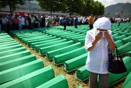 A Muslim woman mourn by the coffins of 775 newly identified victims of the 1995 Srebrenica massacre, lined up for a joint burial in Potocari July 11, 2010. Each year, bones are matched to a name and buried in a mass funeral on July 11, the anniversary of the Srebrenica massacre of up to 8,000 Muslim men and boys by Bosnian Serb forces. REUTERS/Marko Djurica