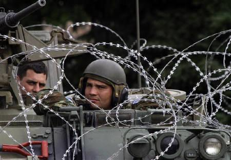 NATO peacekeepers from Greece watch out from their armoured vehicle in Mitrovica July 2, 2010.  REUTERS/Hazir Reka/Files