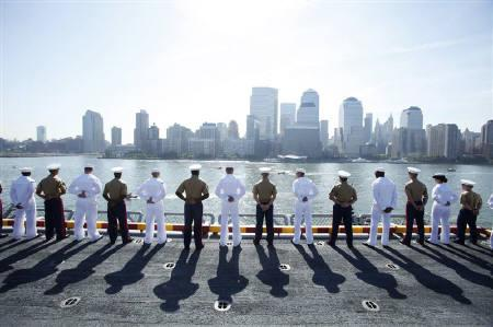 U.S. Marine Corps and Navy personnel salute at the rails of the USS Iwo Jima as the amphibious assault ship passes Ground Zero in New York Harbor for Fleet Week May 26, 2010.  REUTERS/Lucas Jackson/Files