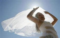 """<p>A married woman dressed in a wedding dress poses for a picture during the 3rd """"Parade of Brides"""" in the centre of Russia's Siberian city of Krasnoyarsk, June 20, 2010. REUTERS/Ilya Naymushin</p>"""