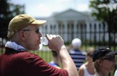 <p>A tourist drinks water as he stands in the heat outside the White House in Washington, July 24, 2010. REUTERS/Jonathan Ernst</p>