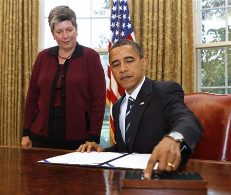 President Obama reaches for a pen to sign the Southwest Border Security Bill, as Secretary of Homeland Security Janet Napolitano watches, in the Oval Office, August 13, 2010. REUTERS/Larry Downing