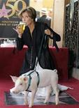 <p>Emma Thompson drinks a pint from the pub her star is in front of as she poses with Monkey the Pig after being honored with a star on the Hollywood Walk of Fame, August 6, 2010. REUTERS/Gus Ruelas</p>