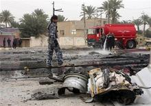 <p>Iraqi policemen and fire fighters perform at the site of bomb attacks in Ramadi, 100 km (60 miles) west of Baghdad December 30, 2009. REUTERS/Yasser Faisal</p>
