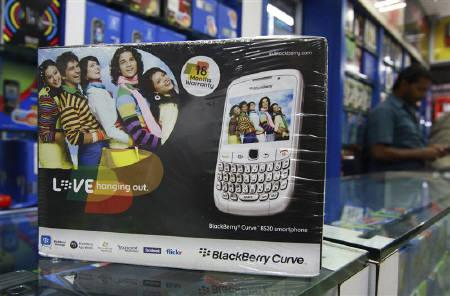 A salesman is seen behind the box of a blackberry handset at a shop in Kochi August 18, 2010. REUTERS/Sivaram V.