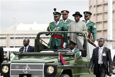 <p>Nigerian president Goodluck Jonathan (R) stands with military aides in a parade convoy during Army Day celebrations in the capital Abuja July 6, 2010. REUTERS/Afolabi Sotunde</p>