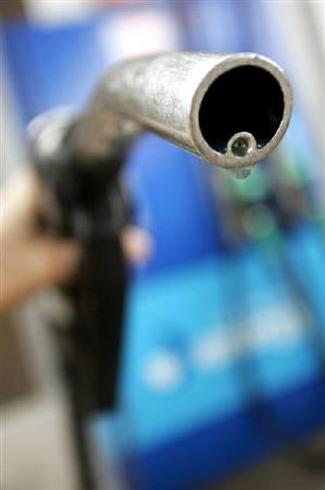 A motorist holds a fuel pump at a petrol station in London, April 18, 2006. REUTERS/Luke MacGregor/Files