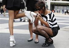 <p>A woman applies lipstick as she arrives at the Lincoln Center to attend the New York Fashion Week, September 9, 2010. REUTERS/Kena Betancur</p>