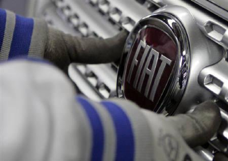 A worker adjusts the logo on a new Fiat Punto at a Fiat factory assembly line in the central Serbian town of Kragujevac, some 120 km south of Belgrade, March 18, 2010. REUTERS/Ivan Milutinovic/Files