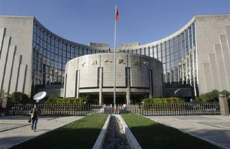 A woman walks in front of the headquarters of the central bank of the People's Republic of China in Beijing October 8, 2008.  REUTERS/Jason Lee/Files