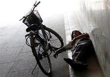 <p>A man sleeps in a tunnel with one arm resting on a pedal of his bike in central Beijing August 25, 2010. REUTERS/David Gray</p>