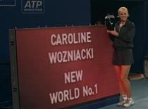 <p>Датская теннисистка Каролин Возняцки позирует для фотографов рядом с табло, информирующим, что она стала первой ракеткой мира 7 октября 2010 года. Каролин Возняцки станет первым представителем Дании на вершине мирового рейтинга WTA после того, как в четверг обыграла чешскую теннисистку Петру Квитову в четвертьфинале China Open со счетом 6-3, 6-2. REUTERS/Petar Kujundzic</p>