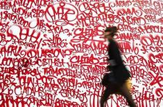 <p>A woman walks by a mural along Houston Street in New York, September 29, 2010. REUTERS/Shannon Stapleton</p>
