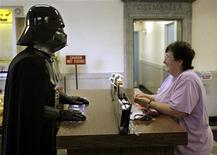 <p>A man, dressed as Darth Vader from the Star Wars movies, talks to Ellen Smith at the U.S. Post Office in Norwood, Massachusetts May 25, 2007. REUTERS/Brian Snyder</p>