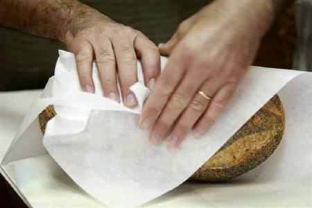 A baker wraps a loaf of bread in paper in his North Sydney Bakery September 18, 2007. Starch grains found on 30,000-year-old grinding stones suggest that prehistoric man may have dined on an early form of flat bread, contrary to his popular image as primarily a meat-eater. REUTERS/Tim Wimborne/Files