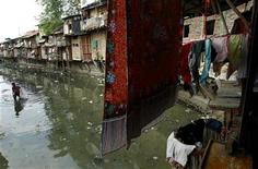 <p>A man collects plastic for recycling in a polluted river in a Jakarta slum October 1, 2010. REUTERS/Beawiharta</p>