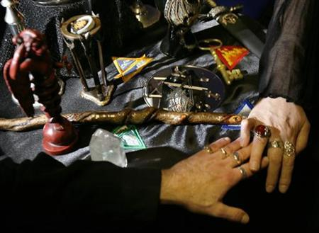 High priestess and priest Richard (L) and Gypsy Ravish hold hands at an altar dedicated to ''magick and the return of the old ways'' at their store Nu Aeon in Salem, Massachusetts October 25, 2006. REUTERS/Brian Snyder