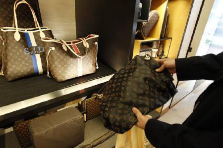 A fake LVMH handbag (R) purchased and shipped from a China -ased online website is pictured next to products on display at a Louis Vuitton store in Chevy ...