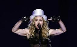 <p>U.S. singer Madonna gestures as she performs during her Sticky and Sweet tour at the O2 Arena in London July 4, 2009. REUTERS/Luke MacGregor</p>