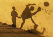 <p>Shadows of children playing soccer are seen on a wall at street in Benguela January 17, 2010. REUTERS/Amr Abdallah Dalsh</p>