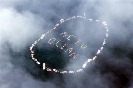 Commercial fishermen and other mariners form the words ''Acid Ocean'' during an event held to spread the message of saving the oceans from acidification caused by fossil fuel emissions, in Homer, Alaska, September 6, 2009. REUTERS/Lou Dematteis/Files
